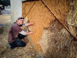 Mike placing the first coat of mud on the straw bales